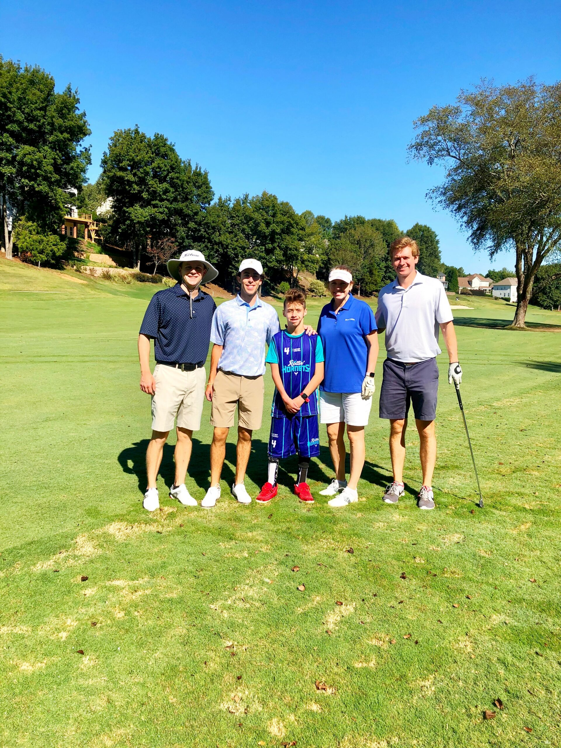 Erica, Shane, Dawson, Zach pose on the green with a player from the rollin hornets